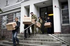 Полицейские выносят документы, изъятые в ходе обыска в клиниках немецкого Красного Креста.